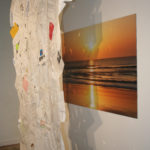 Paper Collage hanging in front of Image of a sunset