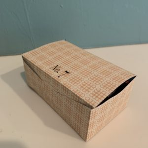 """Closed paper box. """"No.7"""" on the lid."""