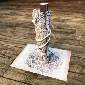 Paper cylinder with paper and rope wrapped around it.