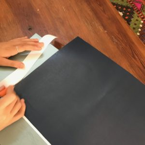 Cutting out a black sheet of paper.