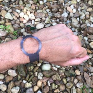 A paper watch on a wrist with a background of pebbles.