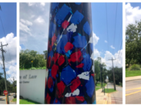 """Vinyl wrapped wayfinding poll that depicts Brinda Pamulapati's installation of the acrylic painting """"Blossoms"""" (2016). Red, blues, whits and yellows make up the abstract bouquet."""